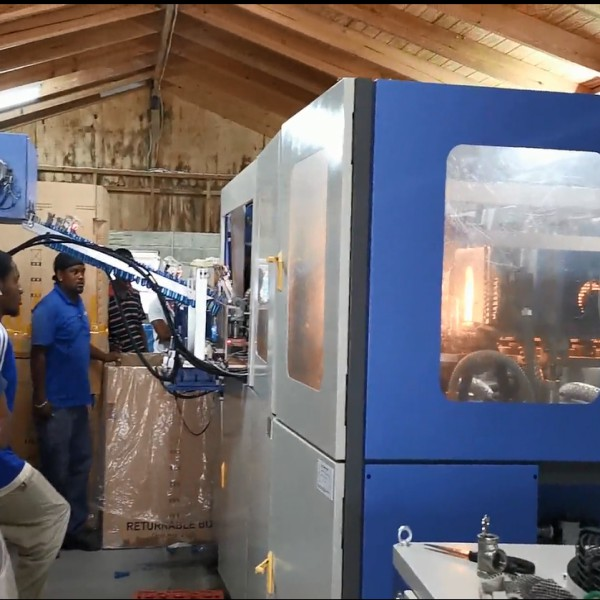 Company engineers are testing automatic plastic bottle blowing machine for customers-J&D WATER